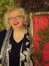Liz beside red door CROP 300